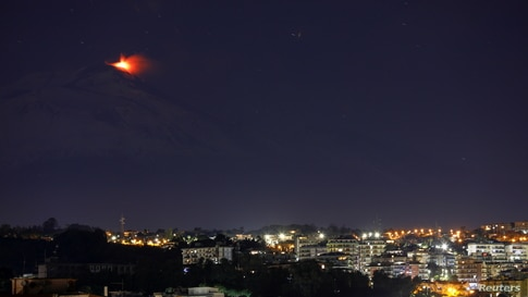 An eruption from Mount Etna lights up the sky during the night, seen from Catania, Italy, Jan. 4, 2021.