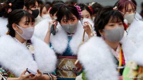 Kimono-clad youth wearing protective face masks leave their Coming of Age Day celebration ceremony at Yokohama Arena in Yokohama, south of Tokyo, Japan, amid the COVID-19 pandemic.