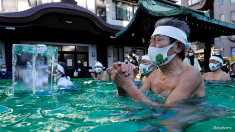 Participants pray as they take an ice-cold bath during a ceremony to purify their souls and to wish for overcoming the COVI-19 pandemic at the Teppozu Inari shrine in Tokyo, Japan.