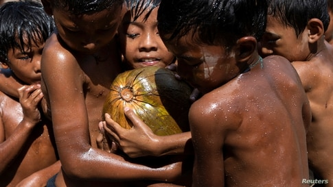 Children play with an oiled coconut during Myanmar's 73rd Independence Day celebrations amid the spread of the COVID-19 in Yangon.