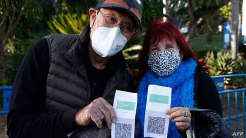 """Israelis show their """"green pass"""" (proof of being fully vaccinated against the coronavirus) before entering the Green Pass…"""