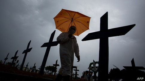 A workers wearing a protective suit and carrying an umbrella walks past the graves of COVID-19 victims at the Nossa Senhora…