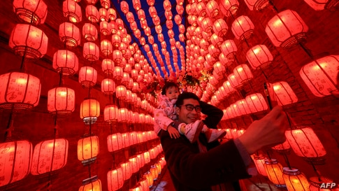People take photos next to a display of lanterns decorated with lights during the Lantern Festival, which marks the end of the…