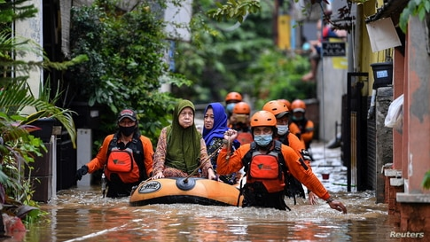 Volunteers evacuate elderly women with an inflatable boat in an area affected by floods, following heavy rains in Jakarta,…