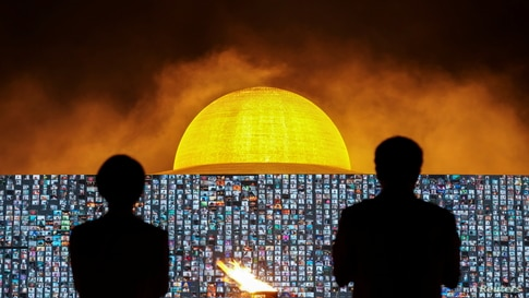 People pray as screens show devotees gathering via Zoom application during a ceremony to commemorate Makha Bucha Day at the Wat…