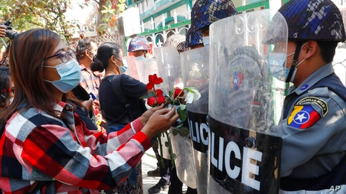 Supporters give roses to police while four arrested activists make a court appearance in Mandalay, Myanmar, Friday, Feb. 5,…