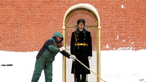 A municipal worker clears snow as an honor guard soldier stands in his station at the Tomb of Unknown Soldier in Moscow, Russia…