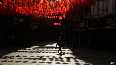 A woman wearing a face mask to curb the spread of coronavirus walks beneath lanterns hung across the street to celebrate the…