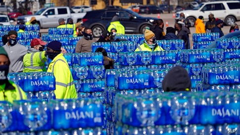 Water to be loaded into vehicles is stacked at a City of Houston water distribution site Friday, Feb. 19, 2021, in Houston. The…