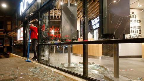 FILE - In this Monday, Jan. 25, 2021 file photo, a man rests on his broom as he stands next to shards of glass and smashed…