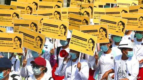 Medicals students display images of deposed Myanmar leader Aung San Suu Kyi during a street march in Mandalay, Myanmar, Friday,…