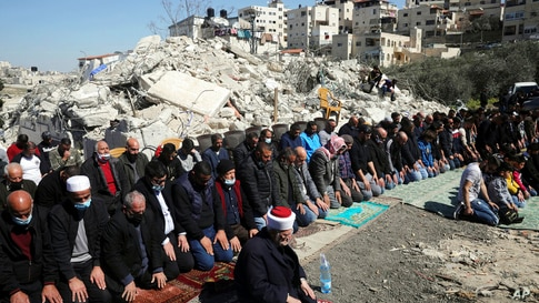 People pray in front of the rubble of demolished Palestinian homes during a protest in Jerusalem, Friday, Feb. 26, 2021. (AP…