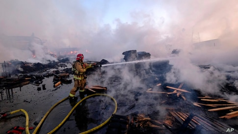A firefighter battles a fire at a commercial yard in Compton, Calif., on Friday, Feb. 26, 2021. A huge fire visible across Los…