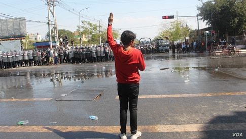A protester flashes the three-finger salute during a protest against the military coup in Mandalay, Myanmar, Feb. 9, 2021.