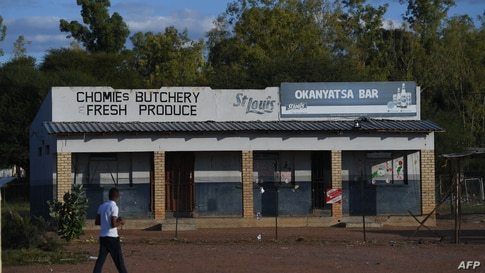 FILE - A man walks past a closed down butcher shop and liquor store amid the coronavirus pandemic, in Gaborone, Botswana, April 5, 2020.