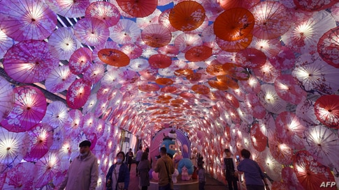 People walk past a display of umbrellas decorated with lights for the upcoming Lantern Festival on a commercial street in Hangzhou, in eastern China's Zhejiang province, Feb. 22, 2021.