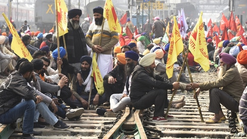 Farmers block railway tracks during a four-hour rail blockade as they continue their protest against the central government's recent agricultural reforms, at a railway station in Amritsar, India.