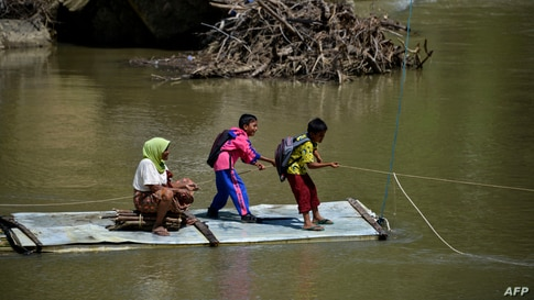Students pull a rope as they use a bamboo raft to cross a river at a village in Siron, Aceh, Indonesia.
