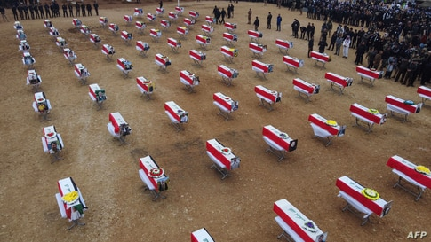 An aerial picture shows mourners gathering around coffins wrapped with the Iraqi flag during a mass funeral for Yazidi victims of the Islamic State (IS) group in the northern Iraqi village of Kojo in Sinjar district, Feb. 6, 2021.