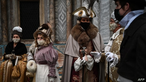 People wearing carnival costumes parade across St. Mark's Square in Venice, Italy, Feb. 6, 2021, despite the carnival is cancelled due to the Covid-19 pandemic.