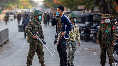 Soldiers carry guns during a clash with protesters demonstrating against the military coup in Mandalay, Myanmar, Feb. 15, 2021.
