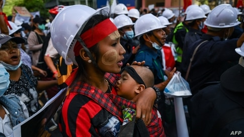 A protester carrying a child, marches during a demonstration against the February 1 military coup in Yangon, Myanmar.