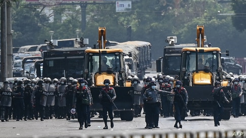 Police advance with heavy construction equipment towards protesters demonstrating against the military coup in Yangon, Myanmar, Feb.22, 2021.