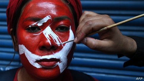 """A supporter of a faction of the ruling Nepal Communist Party (NCP) gets her face painted before taking part in a """"victory"""" rally after Supreme Court ruling to overturn the prime minister's decision to dissolve parliament, in Kathmandu."""