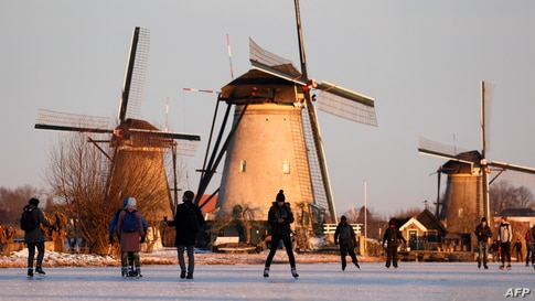 Skaters glide on the ice near windmills in the village of Kinderdijk, Netherlands.