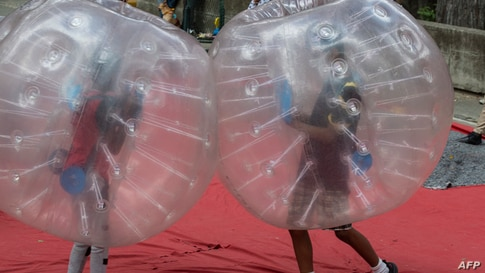 "Two kids inside plastic balloons play at the Los Caobos park, as part of the carnival celebration called ""Carnavales Felices y Bioseguros 2021"" in Caracas, Venezuela, Feb. 15, 2021."