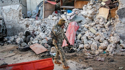 A soldier walks past rubble in the aftermath of an attack on the Afrik Hotel in Mogadishu, Somalia, Feb. 1, 2021. Al-Shabab claimed responsibility for the deadly assault.