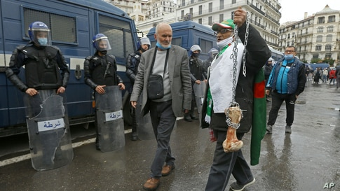 """A man holds a bone while shouting """"That's what's left for those who vote for the President"""" as Algerians demonstrate in Algiers to mark the second anniversary of the Hirak movement."""