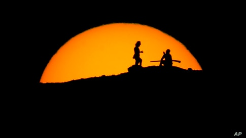 Hikers watch the sunset from a peak at Papago Park, Feb. 20, 2021, in Phoenix, Arizona.