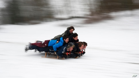 Youngsters slide down hill on sledges after a snowfall at the Woluwe park in Brussels, Belgium.