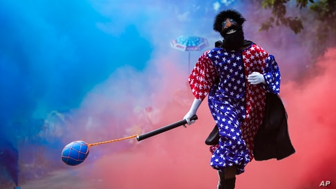 "A member of a ""bate-bola"" or ball hitters group runs past during a brief appearance as part of a Carnival tradition despite COVID-19 restrictions in Rio de Janeiro, Brazil, Feb. 13, 2021."