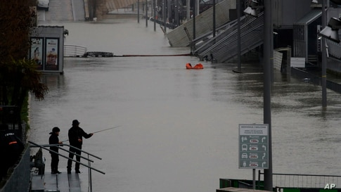 A man and his son fish in the flooded Seine river banks in Paris, France.