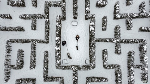 People walk with their dogs in a snow covered Garden maze in Gelsenkirchen, Germany.