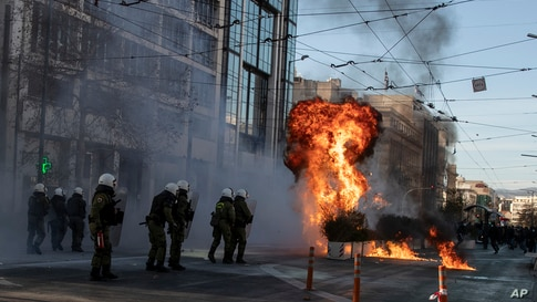Protesters throw a patrol bomb at riot police during a student rally against campus policing, in Athens, Greece.