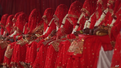 Indian Muslim brides sit during a mass marriage where 63 couples were married in Mumbai.