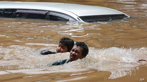 People swim through a flooded neighborhood following heavy rains in Jakarta, Indonesia, Feb. 20, 2021.