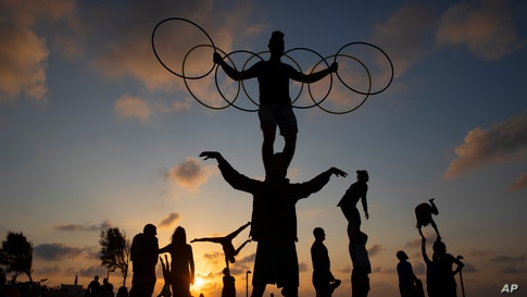 Acrobats perform gymnastic stunts during a nationwide lockdown to curb the spread of the COVID-19 virus at a park in Tel Aviv, Israel, Feb. 6, 2021.