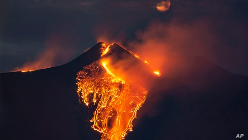 The moon is partially seen in the sky as lava flows from the Mt Etna volcano, near Catania in Sicily, southern Italy.