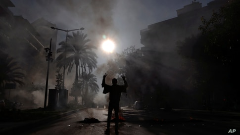 A protester flashes a victory sign as others burn tires to block a road in front of the house of judge Fadi Akiki in Beirut during a demonstration calling for the release of anti-government activists detained in northern Lebanon late last month.