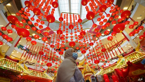 A woman walks under Chinese Lunar New Year decoration at a shopping mall in Kuala Lumpur, Malaysia.