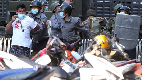 Police arrest a man during a crackdown on anti-coup protesters holding a rally in front of the Myanmar Economic Bank in Mandalay, Myanmar.