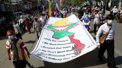 """Anti-coup protesters hold a banner which reads: """"Save Myanmar"""" as they march in Mandalay, Feb. 22, 2021."""