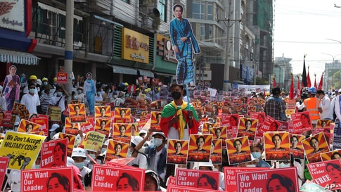 Anti-coup protesters hold up posters with images of deposed Myanmar leader Aung San Suu Kyi during a rally near the Mandalay Railway Station in Mandalay, Feb. 22, 2021.