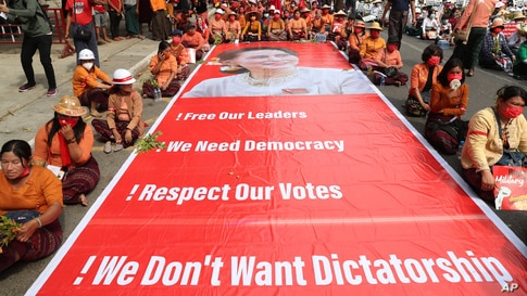 Protesters sit next to a giant banner with images of detained leader Aung San Suu Kyi during an anti-coup protest in Mandalay, Myanmar.