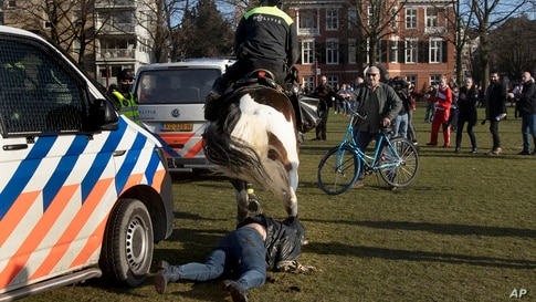 A woman gets trampled by a police horse during a demonstration of several hundreds of people protesting against the coronavirus lockdown and curfew in Amsterdam, Netherlands.