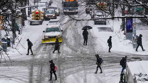 Pedestrians cross 71st Avenue as snow falls in the Queens borough of New York.